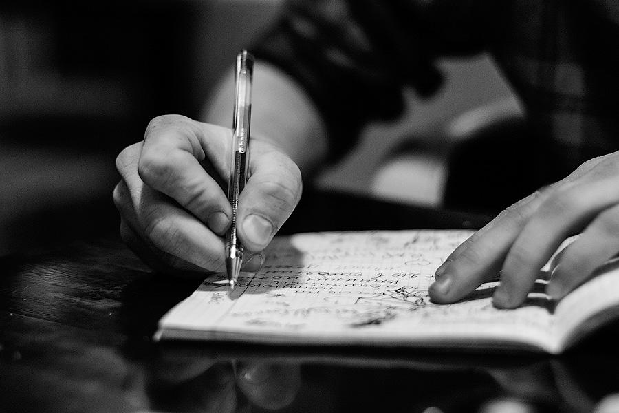 человек что-то пишет, стих или книгу